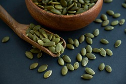 pumpkin seeds in a wooden bowl and vintage scoop. Close up on a black background. copy space for text