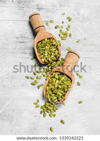 Pumpkin seeds in a wooden scoops. On a rustic background. #1339242221