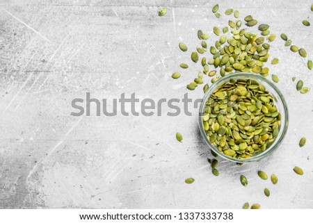 Pumpkin seeds in bowl. On a rustic background. #1337333738