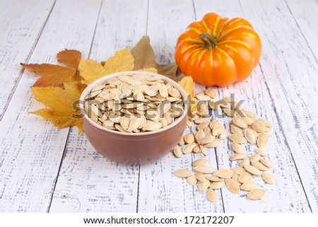 Pumpkin seeds in bowl with pumpkin on wooden background