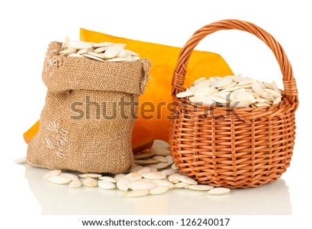 Pumpkin seeds in sack and wicker basket, isolated on white