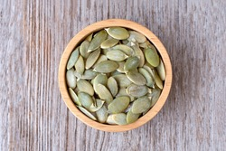 Pumpkin seeds in wooden bowl isolated on wooden table background. Top view. Flat lay.