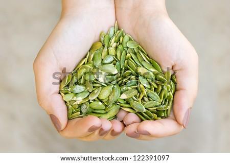 Pumpkin seeds\' kernel in woman hands forming heart shape