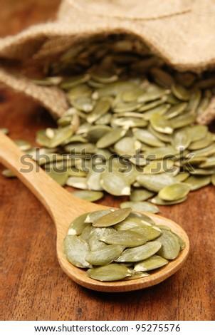Pumpkin seeds on a wood spoon