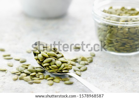 Pumpkin seeds on and beside spoon, close up Foto stock ©