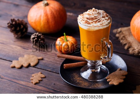 Pumpkin smoothie, spice latte. Boozy cocktail with whipped cream on top on a wooden background