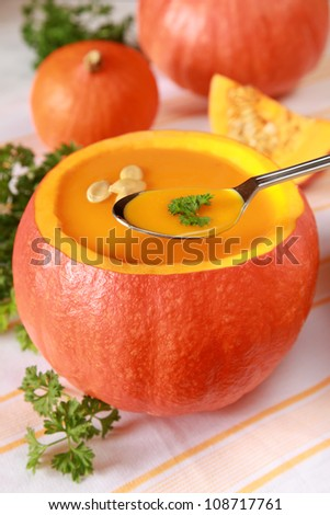 Pumpkin soup in an open pumpkin and more pumpkins in the background.