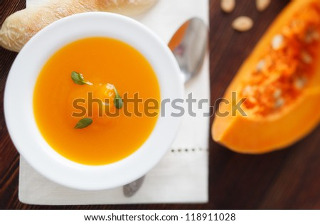 Pumpkin soup in white bowl on wood table