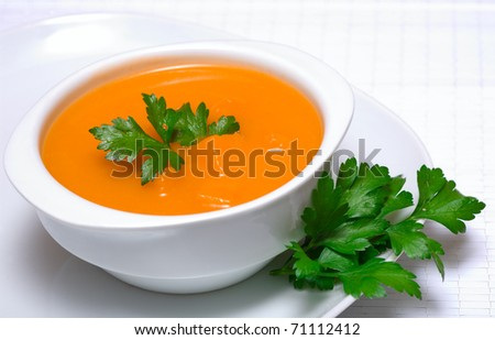 Pumpkin soup in white bowl  with parsley