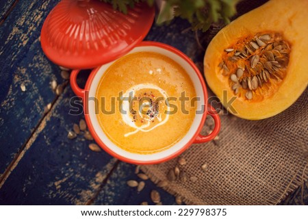 Pumpkin soup on wooden background