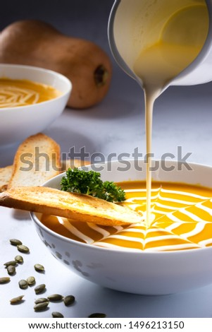 Pumpkin Soup with cream being poured into the bowl. Bowl contains a cream pattern. Toasted baguette included in the bowl and on the side of the bowl.