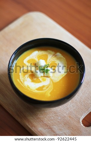 Pumpkin soup with cream, crackers and dill