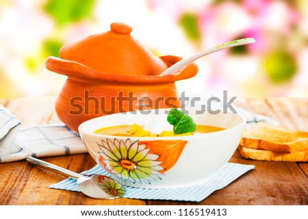 Pumpkin soup with cream in a bowl with painted flower and toast as a garnish.