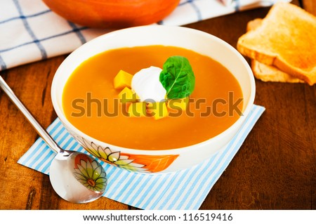 Pumpkin soup with cream in a bowl with painted flower and toast as a garnish on wood table
