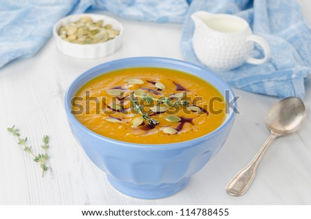 Pumpkin soup with pumpkin oil and seeds - stock photo