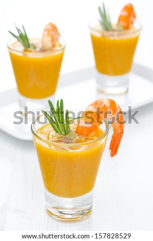 pumpkin soup with shrimp, Parmesan and rosemary in portioned glasses vertical closeup