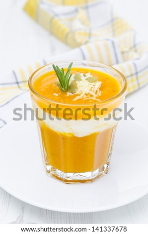 pumpkin soup with shrimp, yogurt and rosemary in a glass vertical