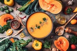 Pumpkin soup with vegetarian cooking ingredients, wooden spoons, kitchen utensils on wooden background. Top view. Vegan diet. Autumn harvest. Healthy, clean food and eating concept. Zero waste