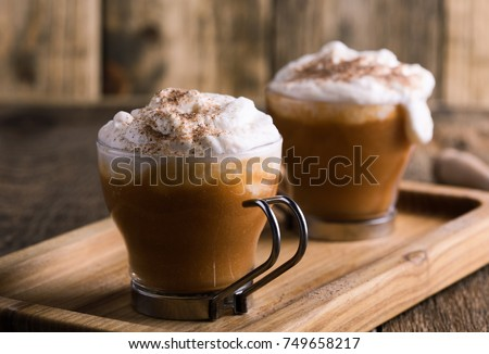 Pumpkin spice latte topped with whipped cream and pumpkin pie spices, traditional fall favorite beverage