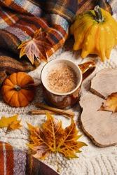 Pumpkin spiced latte or coffee in cup and dry leaves on knit jumper. Autumn or winter hot drink.