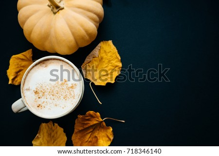 Pumpkin spiced latte or coffee in cup, dry leaves, gifts on black table. Autumn or winter hot drink. Space for text