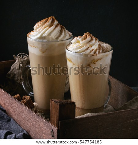 Pumpkin spicy latte  with whipped cream and cinnamon in two glasses standing in wooden box with textile and spices other dark background. Hot sweet coffee drink theme. Square image