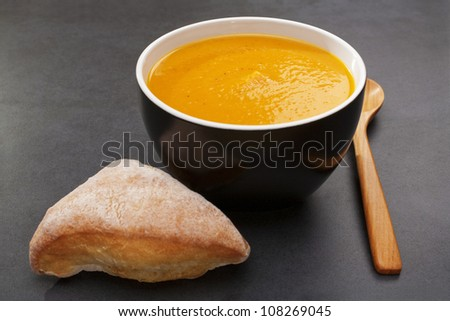 Pumpkin, sweet potato and carrot soup with bread roll and spoon on a dark background, with copy space.