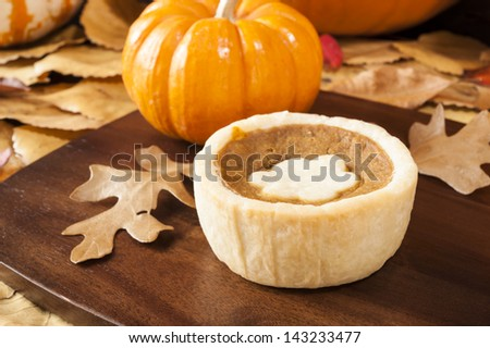 Pumpkin tart surrounded by colorful fall leaves and pumpkins