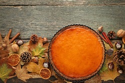 Pumpkin tart with dry leafs on wooden table