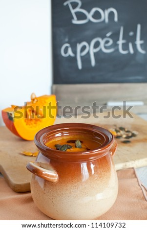Pumpkin vegetable cream soup in brown bowl with piece pumpkin on cutting board