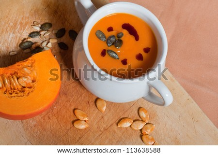 Pumpkin vegetable cream soup in white bowl with pumpkin on cutting board