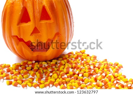 Pumpkin with a carved smiling face on top of candy corn pile.