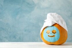 Pumpkin with facial mask and towel on wooden background, copy space