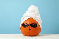 Pumpkin with towel and under eye patches against blue background