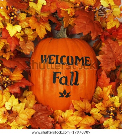 "pumpkin with ""welcome Fall"" surrounded by autumn leaves"