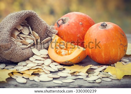 Pumpkins and canvas bag with pumpkins seeds on wooden table. Selective focus.