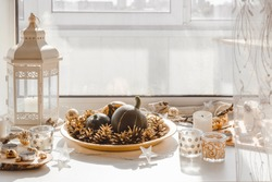 Pumpkins and cones on a golden tray and candles in glass glasses. Autumn window sill decoration. Autumn decor.