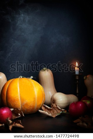 Pumpkins, apples, dry leaves on a table with candles and smoke. Autumnal composition, Thanksgiving, Halloween. Front view. Black background. Copyspace. Vertical