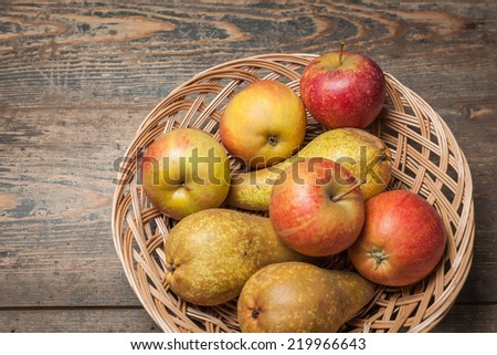 Pumpkins, apples, pears, tomatoes and basket on a wooden plate.