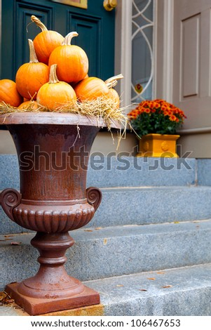 Pumpkins arranged in a large urn by the front door.  Seasonal display for fall.