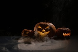 Pumpkins with carved grimaces and candles inside in the dark for halloween. Jack o latern in smoke.