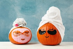 Pumpkins with eye patches and towels on blue background