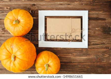Pumpkins with white frame for picture and brown paper package tied up with strings inside over wooden background. Thanksgiving and Halloween concept. View from above.