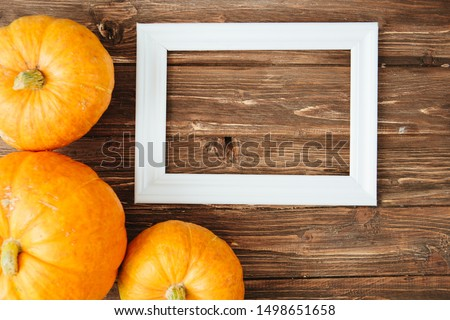 Pumpkins with white frame for picture over wooden background. Thanksgiving and Halloween concept. View from above. Top view. Copy space for text and design