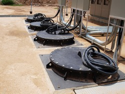 Pumps in the sewage pumping station. Electrical wires and black metal cover of Submersible Pump on outdoor concrete tank. For drainage of municipal sewage or rainwater. Selective focus