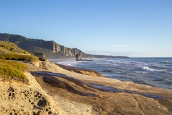 Punakaiki, New Zealand - March 18, 2015: View of Punakaiki beach with special rock formation in the background.