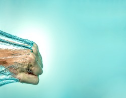 Punch fist in the water from the side. The power of strength, self-confidence, independence. Blue background. Close-up.