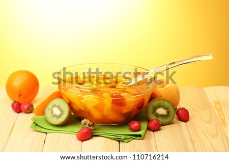 punch in glass bowl with fruits, on wooden table, on yellow background