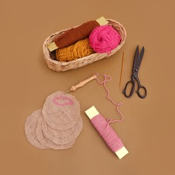 Punch needle embroidery project tools including a black old scissors, colorful threads and jute fabric pieces with a wooden punch needle, top view arts and crafts concept image on brown background