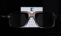 Punched eyeglasses for vision training. Glasses for vision correction. Medical pinhole glasses. Perforated training glasses, eye exam chart on the background, bad eyes concept